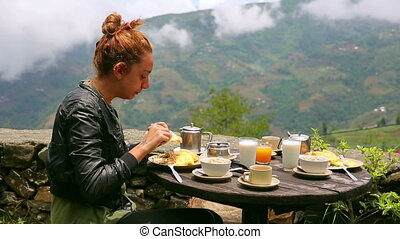 Female tourist eating breakfast eating breakfast at himalayas mountain, Nagarkot, Kathmandu, Nepal