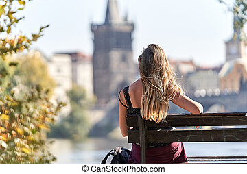 Female tourist in Prague in a bench