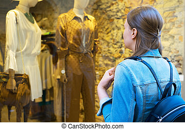 Female tourist looking at the shop window of clothing store.