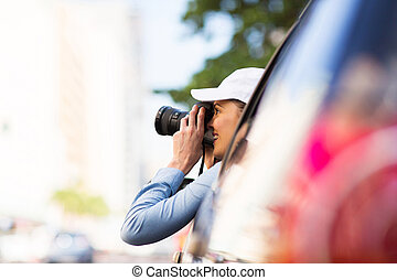 female tourist on road trip and taking photos outside of car...