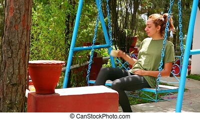 Female tourist on swing drinking coffee