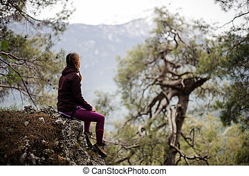 Female tourist sits on a cliff in forest