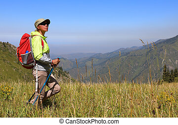 Female tourist stands in the middle of a meadow