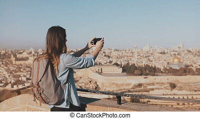 Female tourist takes photos of Jerusalem old town. Pretty Caucasian traveler woman smiling with backpack. Israel. 4K.