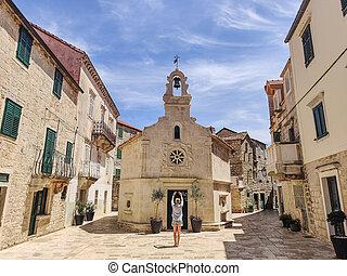 Female tourist taking photo of mall church on square of small urban village of Stari grad on Hvar island in Croatia, Adriatic Sea, Europe