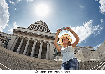 young adult blonde woman taking picture with digital camera in Havana, Cuba. Horizontal shape, waist up, low angle