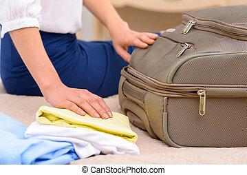 Female tourist unpacking her baggage.