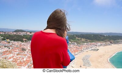 Female tourist using coin paid binoculars on high hill and looking at cityscape of Nazareth, Portugal