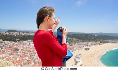 Female tourist using coin paid binoculars on high hill and looking at cityscape of Nazareth, Portugal, slow motion