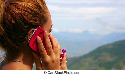 Female tourist using mobile phone on top of mountain