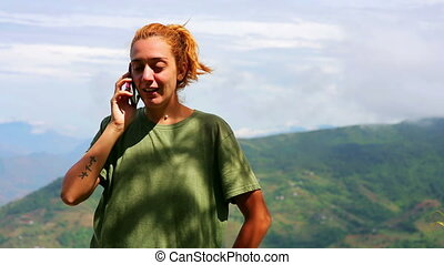 Female tourist using mobile phone on top of mountain at Nagarkot, Kathmandu, Nepal