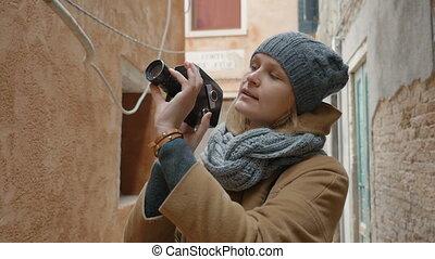 Female tourist using retro video camera outdoor