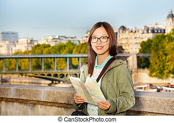 Female tourist walking along embankment with map
