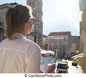 Female tourist with map visiting the city of Split.