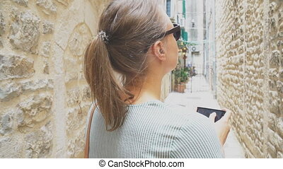 Female tourist with mobile phone lost in the old town.