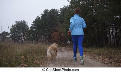 Female trail runner with pet jogging in the wood