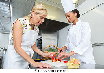 Female trainee chef chopping peppers