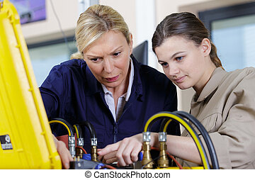 female trainee with mentor working at construction site