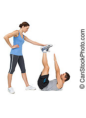 Female trainer assisting man with exercises
