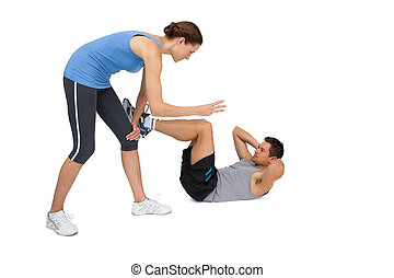 Female trainer assisting man with crunches