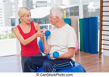 Female trainer assisting senior man in lifting dumbbells