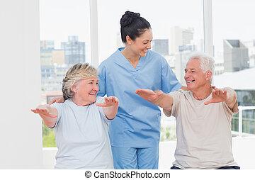 Female trainer assisting seniors - Happy female trainer...
