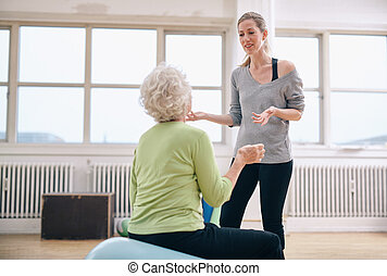 Female trainer discussing progress with elderly woman