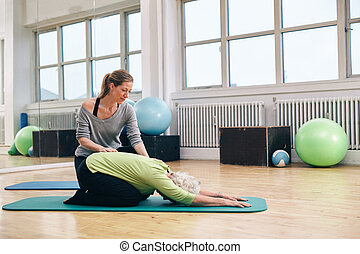Female trainer helping senior woman doing yoga