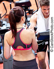Female trainer holding a chronometer while man exercising on a bicycle in a fitness center