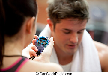 Female trainer holding a chronometer while man doing physical exercise in a fitness center