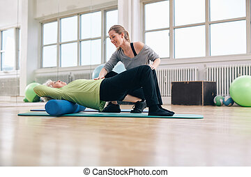Elder woman doing pilates workout with personal instructor