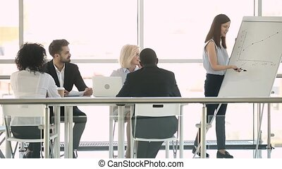 Female trainer speaking at office meeting giving business presentation