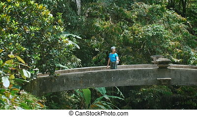 Female traveler in casual blue clothing turning on the bridge and holding selfie-stick in her hands. Attractive brunette making panoramic photo inside of luxuriant vegetation in the tropical jungle.