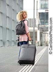 Female traveler looking over shoulder
