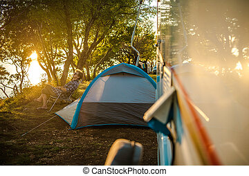 Female Traveler Relaxing Outside Of Camper Van.