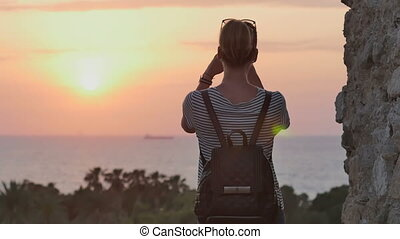 Female traveler with backpack taking photo of sunset sea on her phone