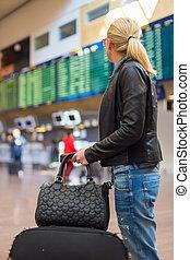 Female traveller checking flight departures board. - ...