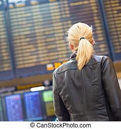 Female traveller checking flight departures board. -...