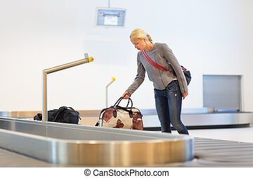 Female traveller collecting luggage at airport.