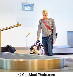Female traveller collecting luggage at airport terminal. -...