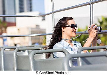 female traveller taking video of the city using digital...