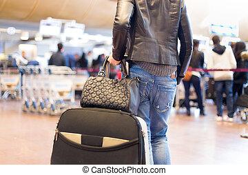 Female traveller walking airport terminal.