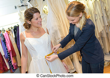 female trying on wedding dress with women assistant