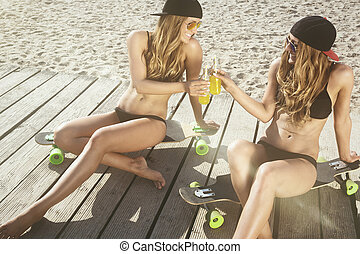 female twins having fun sitting on a skateboard.