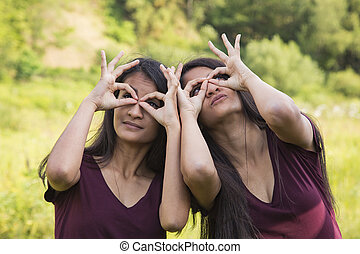 Female twins  look through fingers, outdoor shot in summer.