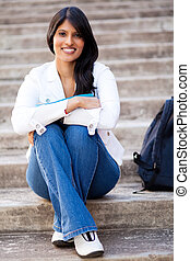female university student sitting outdoors