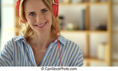 Female university student taking off headphones and smiling