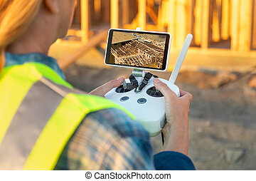 Female Unmanned Aircraft System (UAV) Quadcopter Drone Pilot with Controller Inspecting New House Framing.
