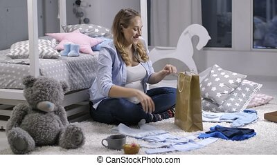 Female unpacking shopping bag with baby clothes