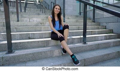Female urban athlete sitting on stairs after outdoor workout. Sporty woman wearing fashion sport black leggings and blue shirt